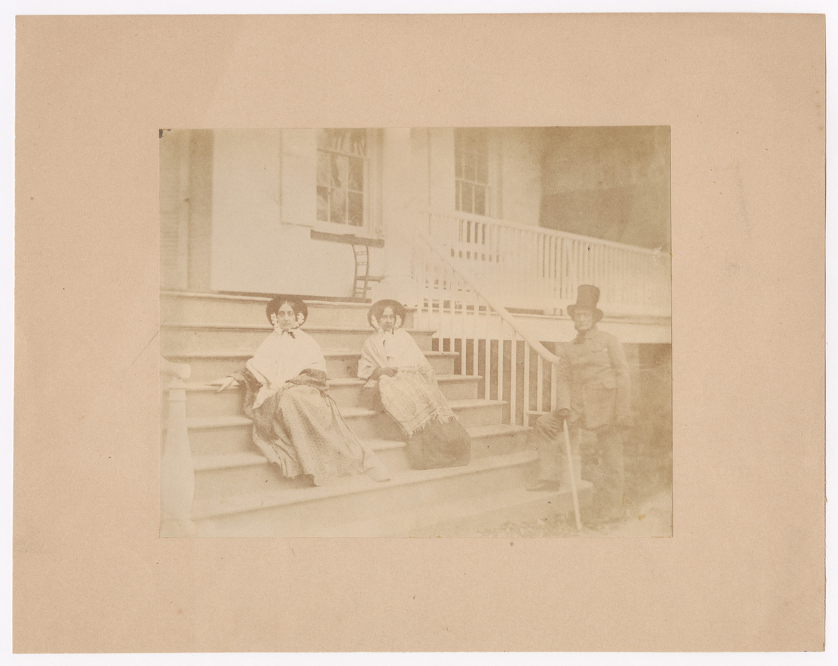 Two Women Seated on Porch Step with Man Standng