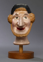 Head of a hand puppet, with blue cap and long nose