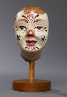 Head of a clown hand puppet, with face painted white, red and black