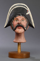 Head of male hand puppet with mutton chops and bicorne hat worn side-to-side