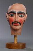 Head of male hand puppet with dark eyes and a painted moustache