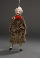 Marionette of old woman with red ribbon around neck