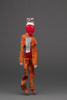 Jigging puppet of male in orange with red cloth over face